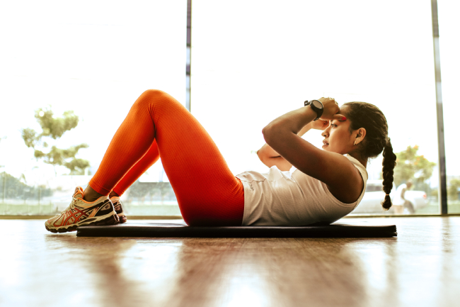 A woman exercises doing a sit up on the floow with a white top and orange leggings